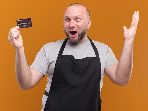 Zaskoczony słowiański w średnim wieku fryzjer męski w mundurze trzymając kartę kredytową podnosząc rękę na pomarańczowej ścianie