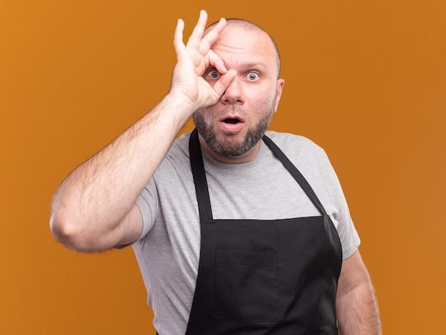 Zaskoczony słowiański w średnim wieku męski fryzjer w mundurze pokazujący gest wygląd na białym tle na pomarańczowej ścianie