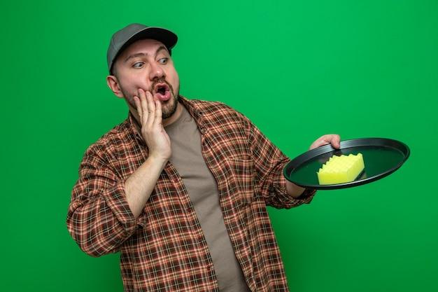 Zaskoczony sprzątacz trzymający i patrzący na gąbkę na talerzu