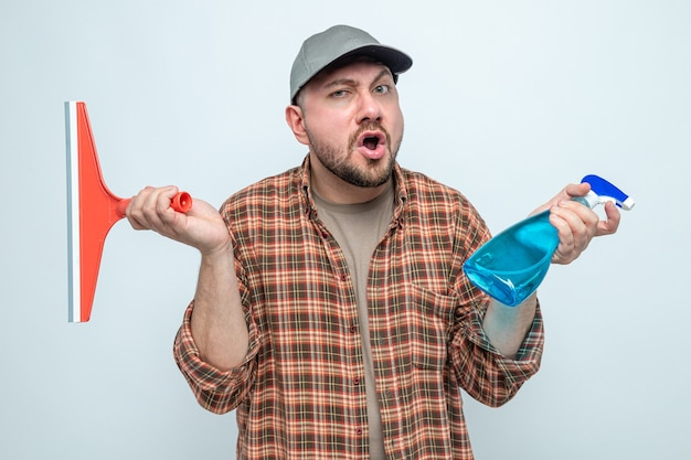 Zaskoczony sprzątacz trzymający ściągaczkę i środek czyszczący w sprayu
