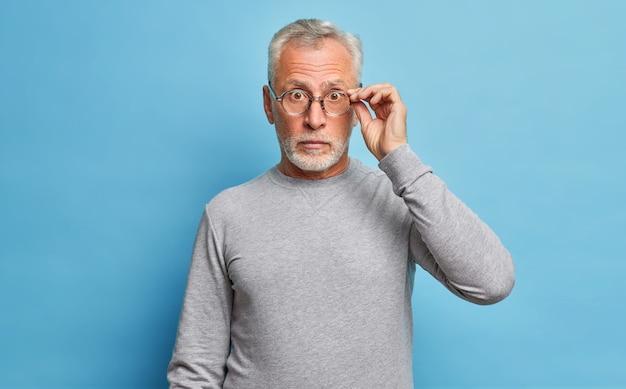 Zaskoczony starszy, brodaty kaukaski mężczyzna patrzy przez okulary, wyrażając szok, cuda sezonowe rabaty i ceny słyszy niesamowite wiadomości, nosi zwykły szary sweter odizolowany na niebieskiej ścianie