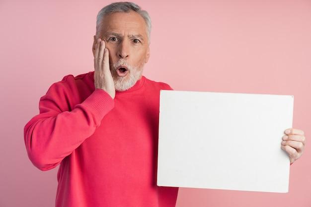 Zaskoczony starszy mężczyzna trzyma białą kartkę papieru