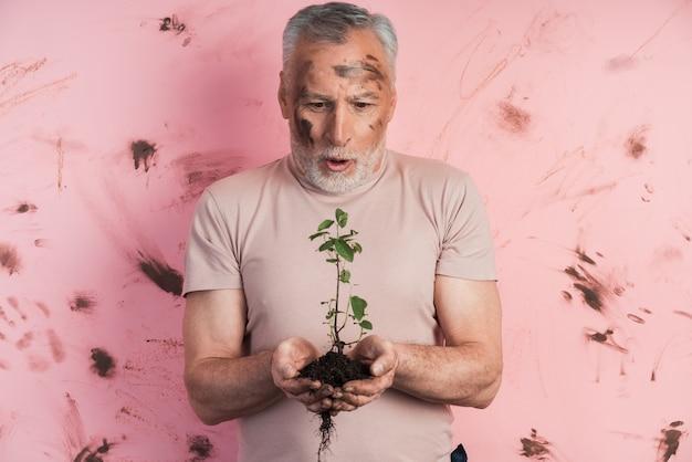 Zaskoczony starszy mężczyzna trzyma roślinę do sadzenia na ścianie brudnej