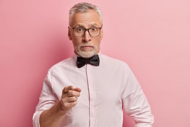 Zaskoczony starszy mężczyzna ubrany w elegancką koszulę z czarną muszką, przezroczyste okulary, wskazuje na aparat, pozuje na różowym tle.