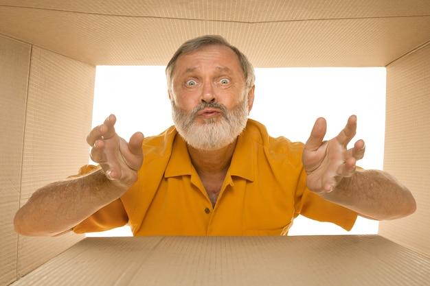 Zaskoczony starszy pan otwierający największą paczkę pocztową
