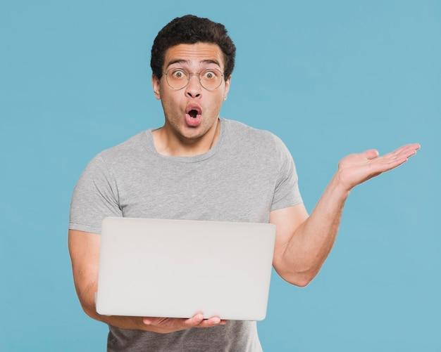 Zaskoczony student uniwersytetu posiadania laptopa