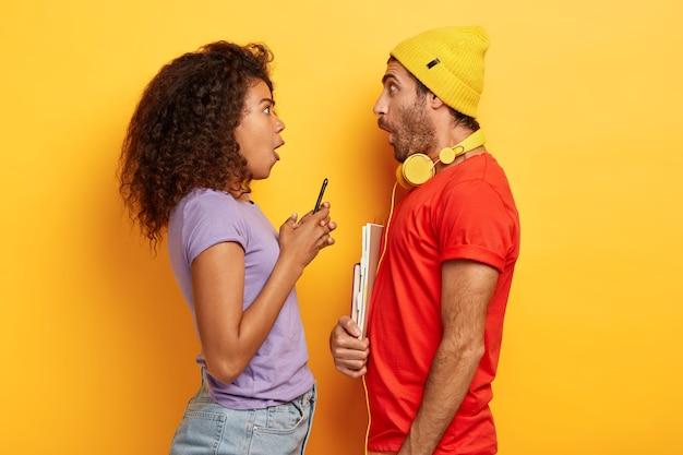 Zaskoczony, stylowa para pozuje na żółtej ścianie z gadżetami