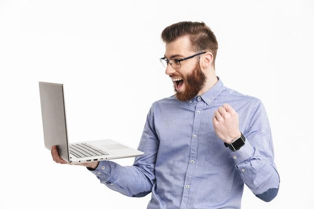 Zaskoczony szczęśliwy brodaty elegancki mężczyzna w okularach przy użyciu laptopa i raduje się