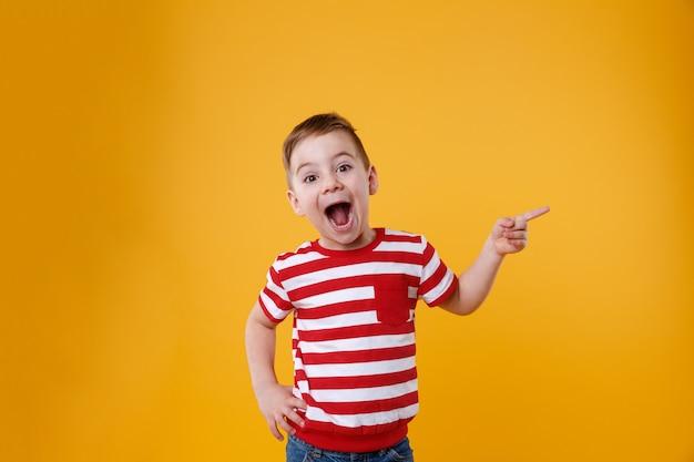 Zaskoczony szczęśliwy chłopak wskazując palcami w górę