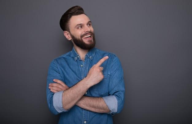 Zaskoczony, szczęśliwy i podekscytowany, uśmiechnięty brodaty facet wskazuje na jakąś reklamę na kopii