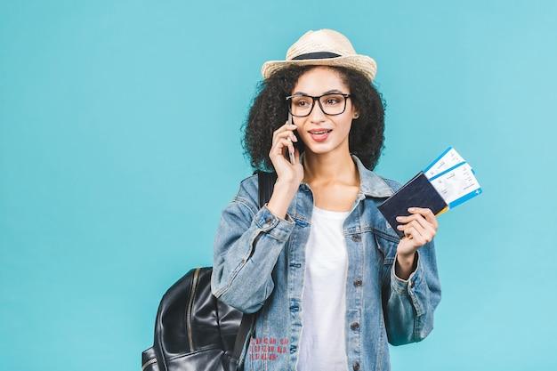 Zaskoczony szczęśliwy młody afroamerykanin dziewczyna na białym tle na niebieskim tle w studio. koncepcja podróży. trzymaj paszport, bilety na kartę pokładową. korzystanie z telefonu.