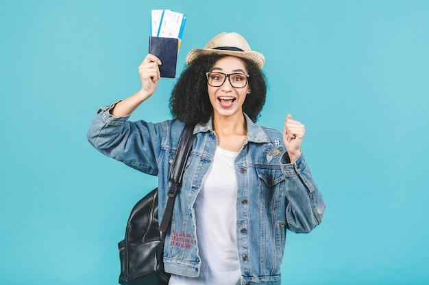 Zaskoczony szczęśliwy młody afroamerykanin dziewczyna na białym tle na niebieskim tle w studio. koncepcja podróży. trzymaj paszport, bilety na kartę pokładową. zwycięzca.