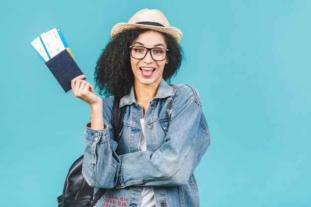 Zaskoczony szczęśliwy młody afroamerykanin dziewczyna na białym tle na niebieskim tle w studio. koncepcja podróży. trzymaj paszport, bilety na kartę pokładową.