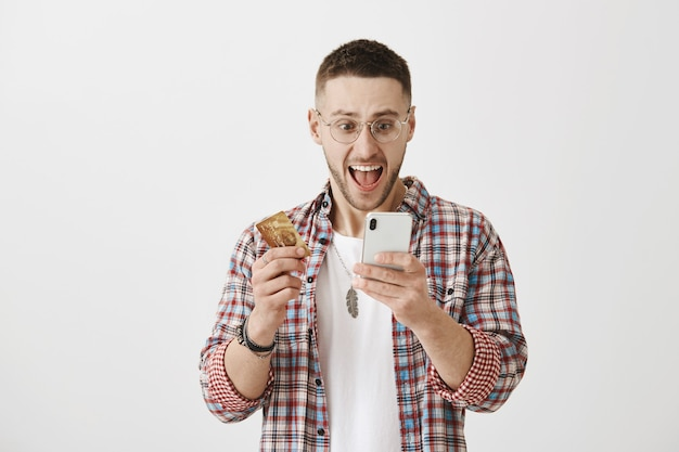 Zaskoczony szczęśliwy młody chłopak w okularach pozuje z jego telefonem i kartą