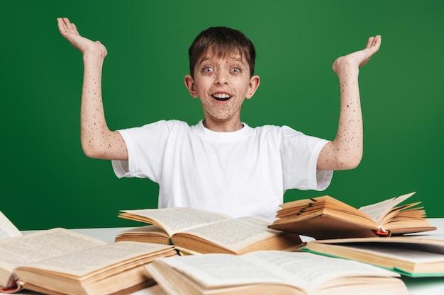 Zaskoczony szczęśliwy młody chłopak z piegami gestykuluje i patrzy z przodu, siedząc przy stole z książkami nad zieloną ścianą