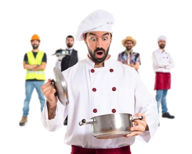 Zaskoczony szef kuchni trzyma garnek