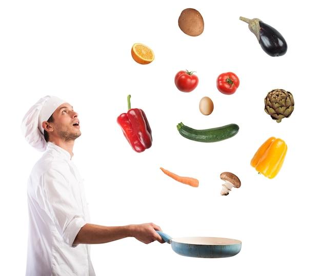 Zaskoczony szef kuchni uśmiecha się podskakując na warzywach na patelni