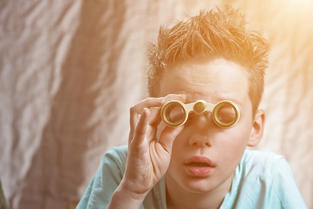 Zaskoczony teen chłopiec emocjonalnie patrząc przez lornetkę