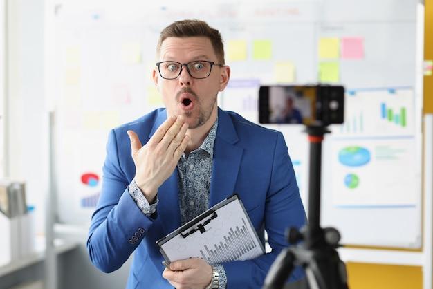 Zaskoczony trener biznesu trzymający dokumenty z wykresami przed kamerą telefonu komórkowego online