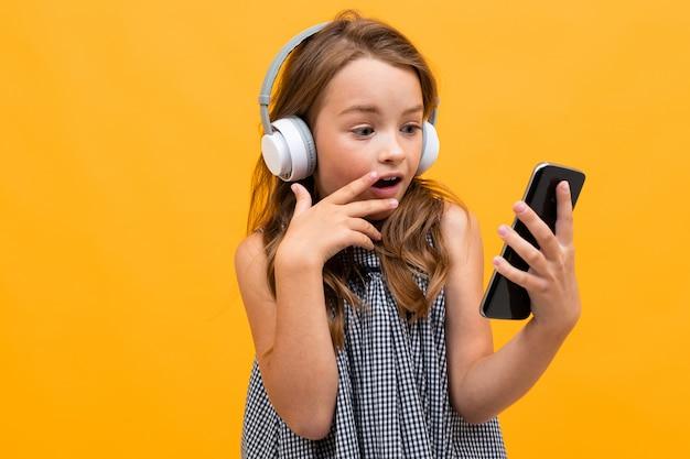 Zaskoczony uczennica patrzy na smartfona na żółtym tle
