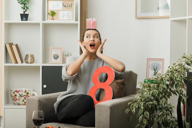 Zaskoczony układanie rąk na twarzy piękna dziewczyna na szczęśliwy dzień kobiet trzymająca prezent na głowie siedzącej na fotelu w salonie