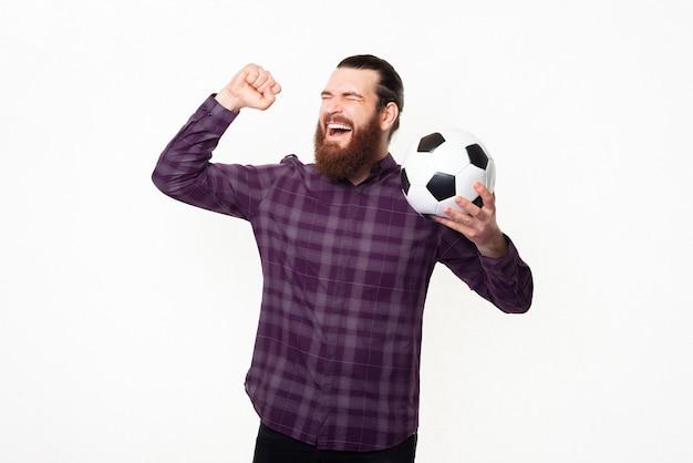 Zaskoczony wesoły mężczyzna w kraciastej koszuli świętuje i kibicuje ulubionej drużynie