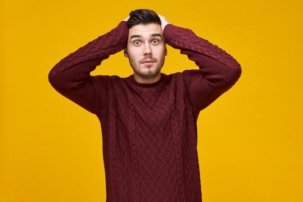 Zaskoczony wyglądający jak robak mężczyzna w ciepłym swetrze trzymający ręce na głowie,
