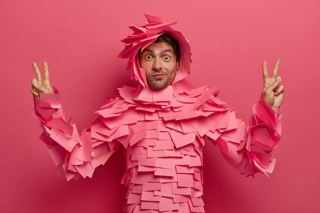 Zaskoczony zabawny mężczyzna bawi się w biurze, pozuje w kreatywnym kostiumie z karteczek samoprzylepnych, podnosi palce w geście zwycięstwa, pokazuje znak pokoju, odizolowany na różowej ścianie. strój papierowy. monochromia