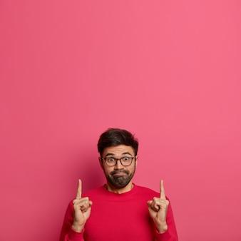 Zaskoczony zaciekawiony mężczyzna naciska usta, reklamuje produkt, wskazuje w górę dwoma palcami wskazującymi