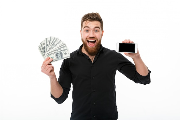 Zaskoczony zadowolony brodaty mężczyzna w koszuli gospodarstwa pieniądze