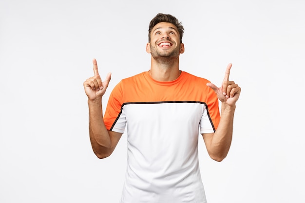 Zaskoczony, zadowolony przystojny brodaty mężczyzna w sportowej koszulce, podnosi głowę i wskazuje w górę