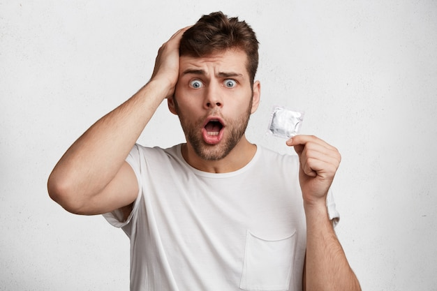 Zaskoczony, zaskoczony mężczyzna wpatruje się w kamerę z nieoczekiwanym spojrzeniem, trzyma prezerwatywę, trzyma szeroko otwarte usta, odizolowane na białym tle. zszokowany zdumiony młody samiec z zarostem dba o bezpieczeństwo.