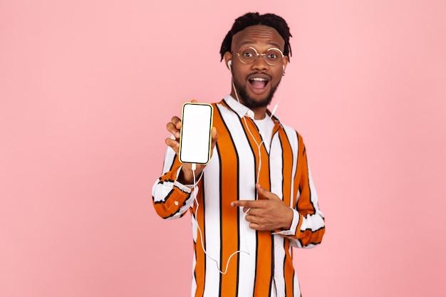 Zaskoczony zdezorientowany mężczyzna wskazujący palcem na smartfona z białym ekranem, reklama