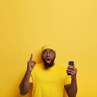 Zaskoczony, zdziwiony mężczyzna w okularach wskazuje palcem wskazującym powyżej, przegląda stronę internetową i przesyła zdjęcie, trzyma szeroko otwarte usta