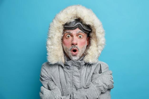 Zaskoczony zmarznięty mężczyzna z czerwoną twarzą drży z zimna obejmuje się, by poczuć ciepłe spojrzenia zepsutych oczu w okularach snowboardowych.