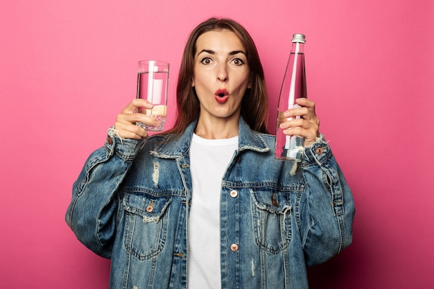 Zaskoczony, zszokowany młoda kobieta trzymająca szklankę wody i butelkę wody na różowej powierzchni