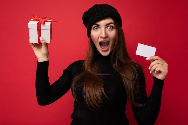 Zaskoczony, zszokowany, zdumiony, piękna, szczęśliwa młoda brunetka kobieta ubrana w czarny sweter i kapelusz na białym tle na czerwonym tle, trzymając kartę kredytową i pudełko patrząc na kamery