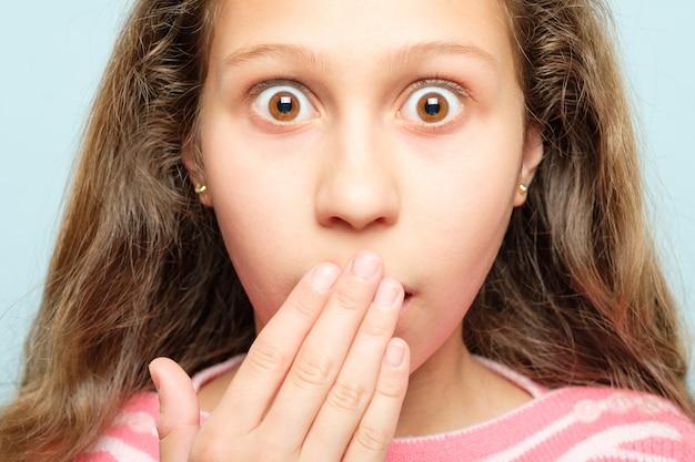 Zaskoczony zszokowany zdumiony zdumiony dziewczyna zakrywający usta. nie do wiary. emocjonalny wyraz twarzy.