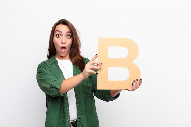 Zaskoczony, zszokowany, zdziwiony, trzymając literę b alfabetu, aby utworzyć słowo lub zdanie.