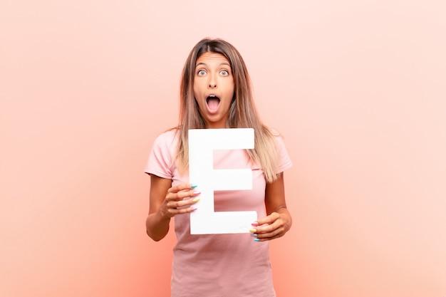 Zaskoczony, zszokowany, zdziwiony, trzymając literę e alfabetu, aby utworzyć słowo lub zdanie.