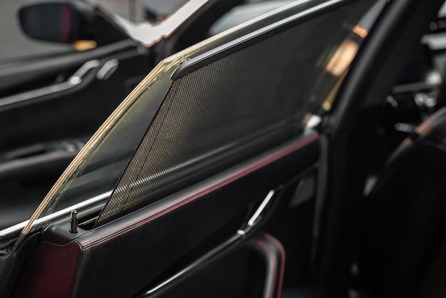 Zasłona boczna tylnej szyby samochodu. zasłona przeciwsłoneczna w nowoczesnym, luksusowym samochodzie. drzwi pasażera. selektywne skupienie.