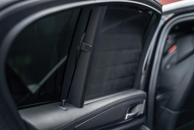 Zasłona boczna tylnej szyby samochodu. zasłona przeciwsłoneczna w nowoczesnym, luksusowym samochodzie. selektywne skupienie.
