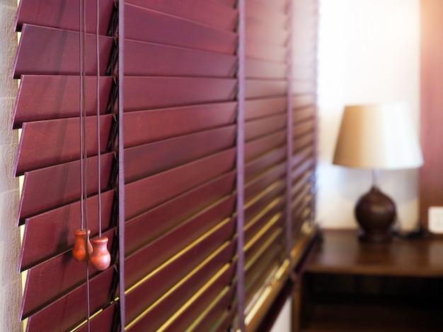 Zasłona okienna z drewnianą żaluzją służy do dekoracji pokoju