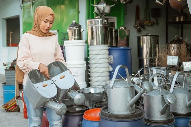 Zasłonięta kobieta stoi trzymając konewkę w sklepie ze sprzętem agd