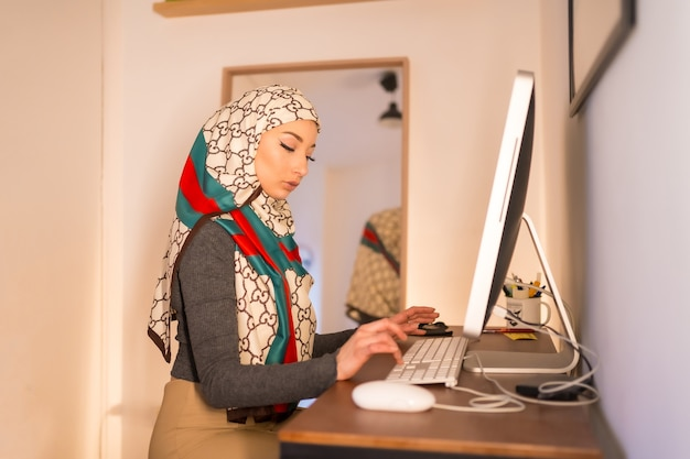 Zasłonięta młoda kobieta na komputerze w domu, pracująca w domu