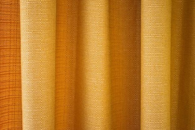 Zasłony z tkaniny w kolorze żółtym z zakładkami. streszczenie tło, zasłony, zasłony złote tkaniny.