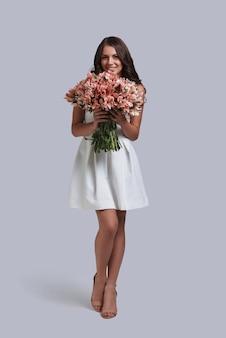 Zasługuje na piękne kwiaty. pełna długość atrakcyjnej młodej kobiety trzymającej bukiet kwiatów, stojąc na szarym tle