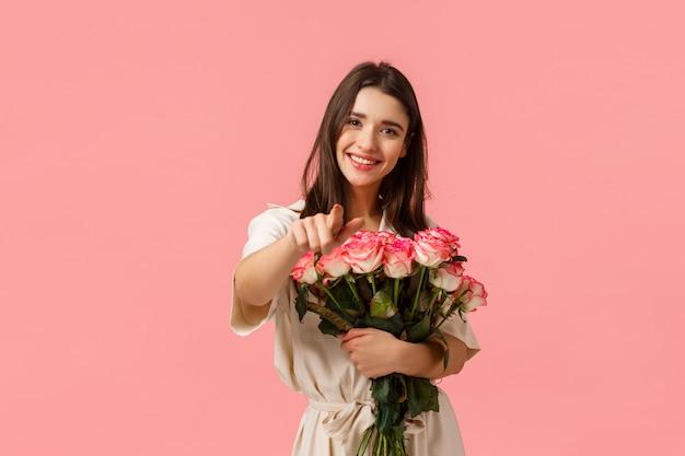 Zasługujesz na najlepiej. urocza śliczna i romantyczna, czuła kaukaska dziewczyna w sukience, trzymająca róże przy piersi, delikatnie zawijająca bukiet i wskazująca palec, uśmiechnięta zachwycona, stojąca różowa ściana