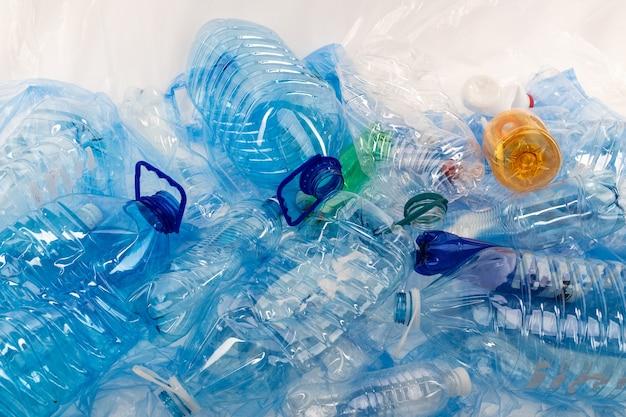 Zaśmiecanie środowiska. butelki o różnych rozmiarach i kolorach układane razem na niebieskiej macie plastikowej i powodujące zanieczyszczenia