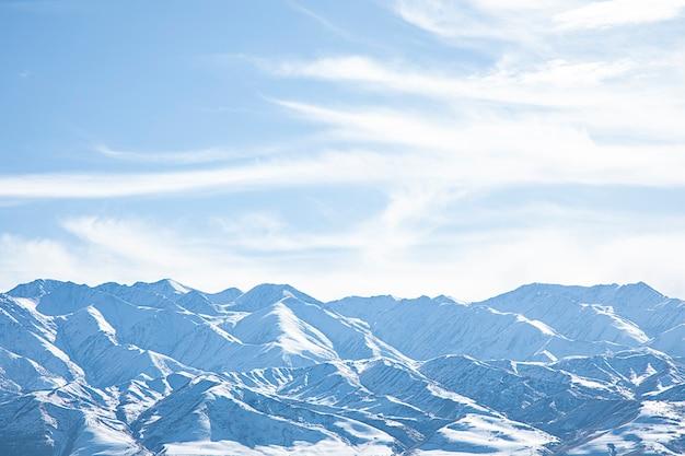 Zaśnieżone góry z niebieskim niebem i chmurami